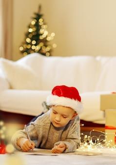 Christmas child escreva uma carta para o papai noel com chapéu de natal escrevendo uma lista de desejos de presente ao lado da árvore de natal
