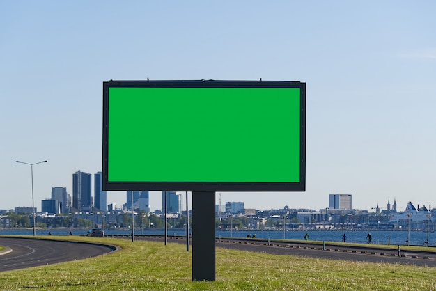 Chroma key outdoor em branco para publicidade ao ar livre em um fundo de paisagem urbana e mar