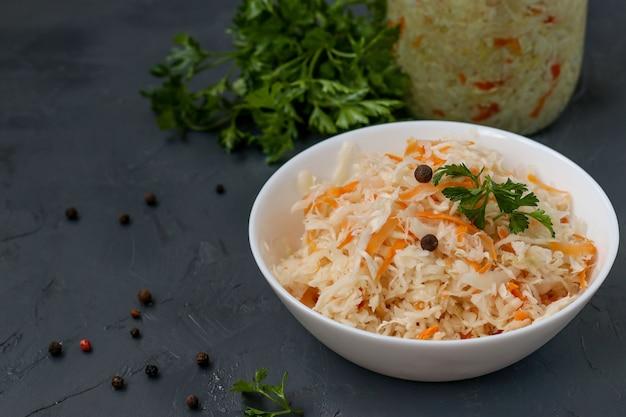 Chucrute caseiro com cenoura e salsa em uma tigela e frasco em um fundo escuro, alimentos fermentados, closeup, cópia espaço