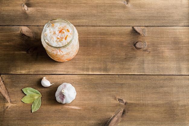 Chucrute caseiro em flatlay de frasco de vidro aberto sobre uma mesa de madeira com espaço de cópia.