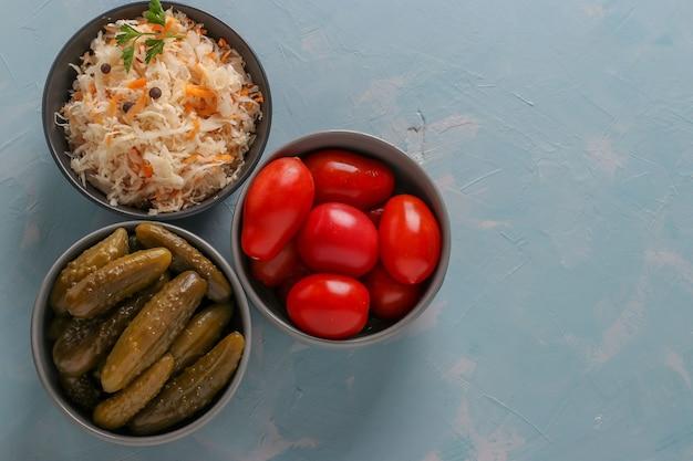 Chucrute caseiro, tomates salgados e pepinos em uma tigela sobre um fundo azul claro, conceito de vegetais fermentados, closeup, vista superior, espaço de cópia