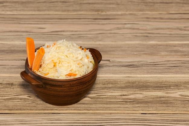 Chucrute com cenouras em uma tigela de madeira