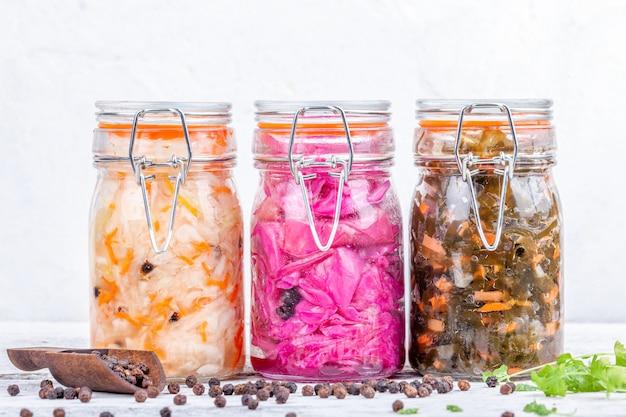 Chucrute marinado caseiro azedo em frascos de vidro na mesa da cozinha de madeira rústica