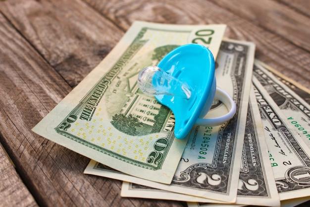 Chupeta azul sobre dinheiro.