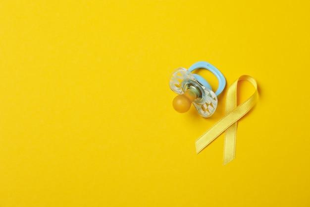 Chupeta e fita de conscientização do câncer infantil em amarelo