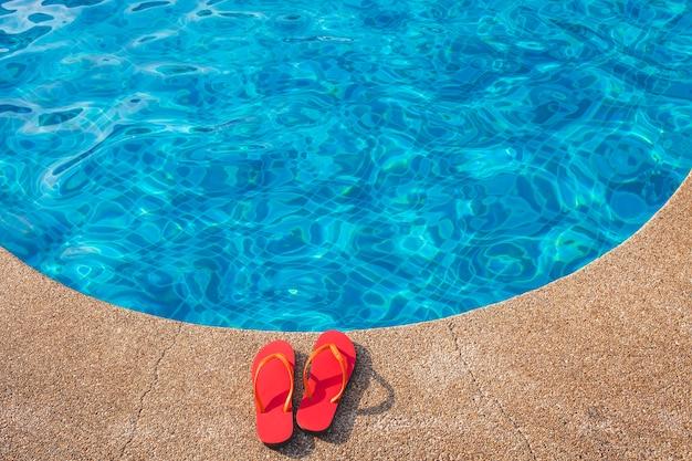 Chupetas vermelhas ao lado da piscina