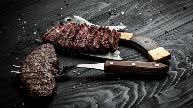 Churrasco americano tradicional bife de alcatra envelhecido seco de fatiado em um açougueiro e garfo. banner, lugar de receita de menu para texto, vista superior.