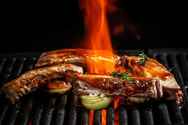 Churrasco assado e costelinha de porco defumada na grelha quente com chamas na superfície preta