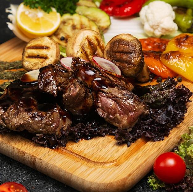 Churrasco, carne grelhada com batatas e batatas fritas vegetais na placa de madeira,