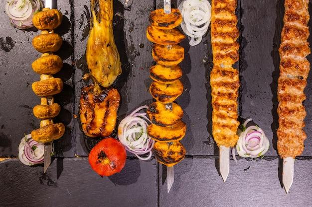 Churrasco colagem pernas de frango costelinha de porco, filé de frango e carne no espeto close-up em um fundo escuro.