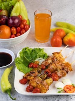 Churrasco com uma variedade de carnes, completas com tomates e pimentões em um prato branco.
