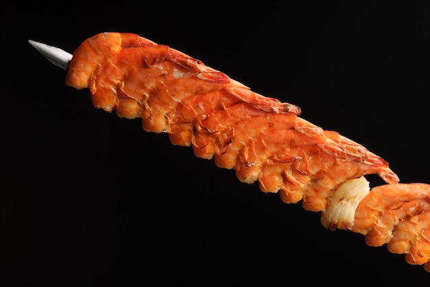 Churrasco de camarão no espeto sobre fundo preto gastronomia brasileira