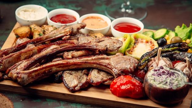 Churrasco de carne com legumes grelhados e variedade de molhos em uma bandeja de madeira.