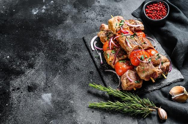 Churrasco de carne de porco e bovino em espetos de madeira