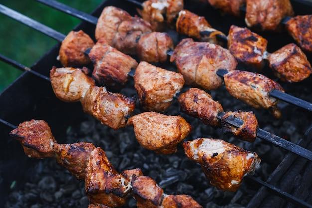 Churrasco de carne de porco é preparado em espetos na grelha
