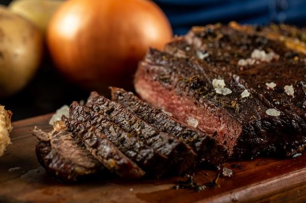 Churrasco de carne fatiada servido com cebola e sal marinho