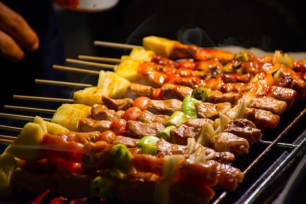Churrasco de carne grelhada com legumes e molhos de tomate nas grades de aço com o calor.