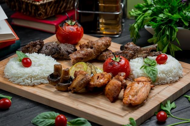 Churrasco de cordeiro e frango com guarnição de arroz em uma placa de bambu