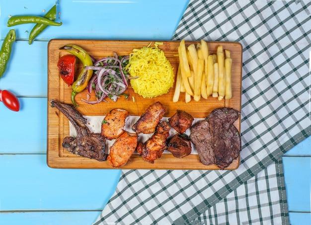 Churrasco de frango e carne com salada de arroz e legumes