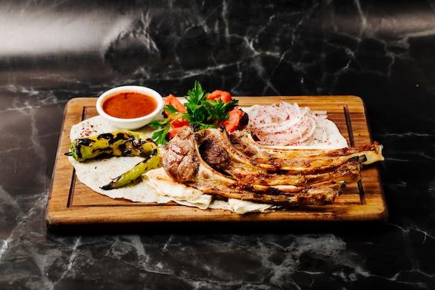 Churrasco de osso de carne em lavash com legumes grelhados e molho vermelho.