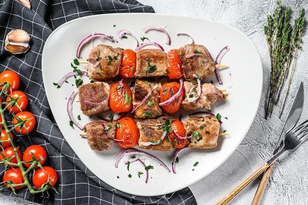 Churrasco de porco e carne bovina em espetos de madeira