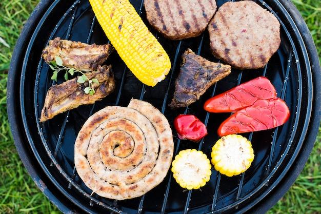 Churrasco de salsichas, legumes e carne no grelhador a carvão