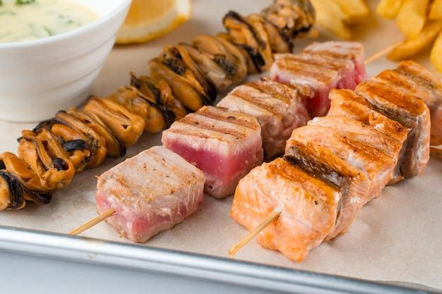 Churrasco no espeto de frutos do mar com mexilhões grelhados, atum, salmão no espeto de madeira com molho branco e limão.
