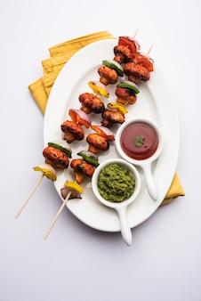 Churrasco ou cogumelo tandoori tikka, servido em prato com chutney verde e ketchup. foco seletivo
