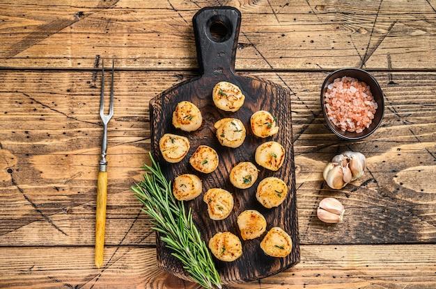 Churrasco vieiras grelhadas com molho de manteiga em uma placa de madeira.