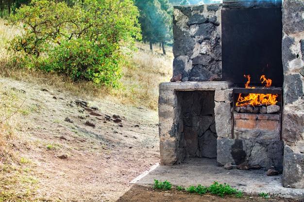 Churrasqueira de pedra, com fogo, ao ar livre.