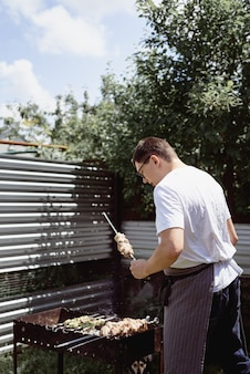 Churrasqueira no quintal. equipa as mãos grelhando kebab e vegetais em espetos de metal.