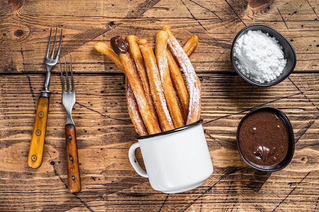 Churros com açúcar e calda de chocolate. fundo de madeira. vista do topo.