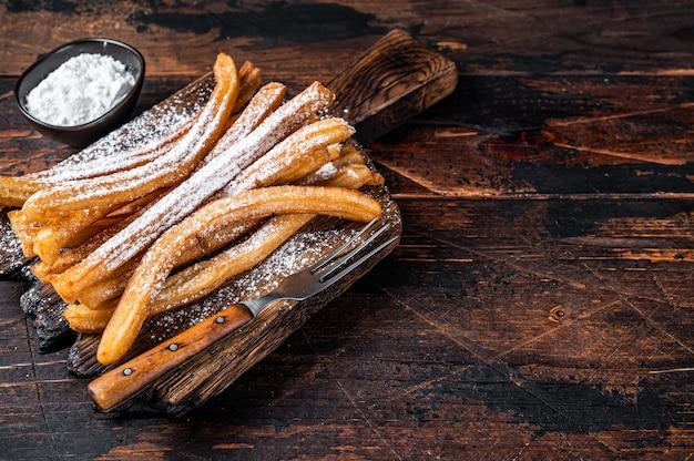 Churros de sobremesa espanhóis com açúcar em pó em uma bandeja de madeira