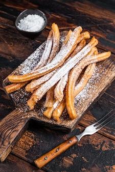 Churros de sobremesa espanhola com açúcar em pó em uma bandeja de madeira. fundo de madeira escuro. vista do topo.