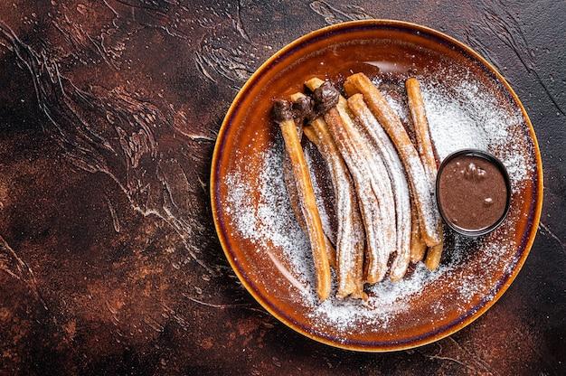 Churros de tapas espanholas com açúcar e calda de chocolate. fundo escuro. vista do topo. copie o espaço.