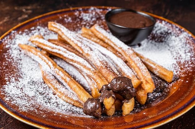 Churros de tapas espanholas com açúcar e calda de chocolate. fundo escuro. vista do topo.