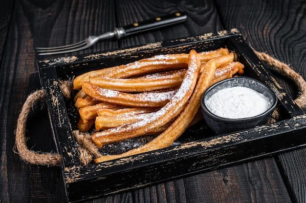 Churros palitos fritos com açúcar em pó em bandeja de madeira