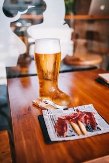 Chuteira de copo de cerveja com deliciosos petiscos de presunto ibérico espanhol em uma mesa de madeira