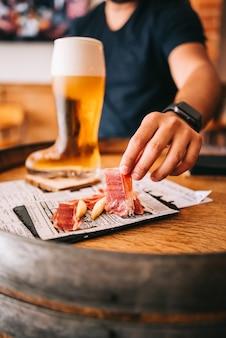 Chuteira de vidro de cerveja com deliciosos petiscos de presunto ibérico espanhol em um barril de madeira