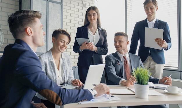 Chuva de ideias. grupo de empresários juntos, olhando para o laptop.