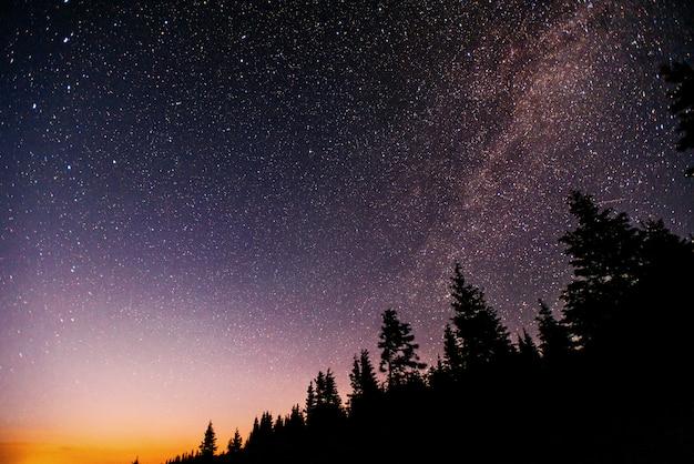 Chuva de meteoros de inverno fantástica e as montanhas cobertas de neve