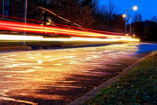 Chuva na luz noturna das vitrines refletida na vista da estrada do nível do asfalto