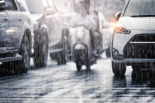 Chuva pesada cair na cidade com carros embaçados. foco seletivo e cores em tons.