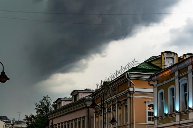 Chuva pesada e nuvens maciças que voam sobre os telhados da cidade de europa