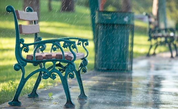 Chuva quente de verão. banco de metal com assentos de madeira em um fundo de parque verde durante a chuva.