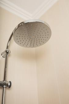 Chuveiro de aço inoxidável no banheiro com azulejos na parede