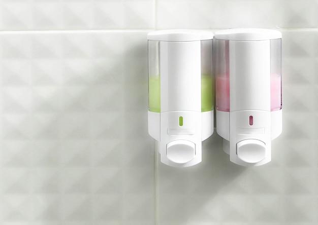 Chuveiro e frasco de xampu na parede