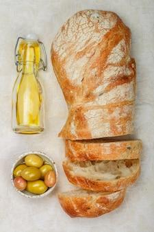 Ciabatta com azeitonas, pão fresco italiano tradicional delicioso fresco, azeitonas e azeite de oliva em uma mesa de madeira branca