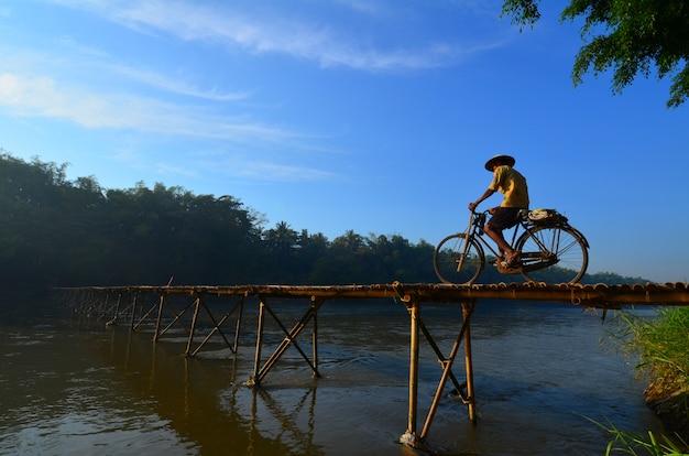 Ciclismo através da ponte de bambu em bantul, java central, indonésia