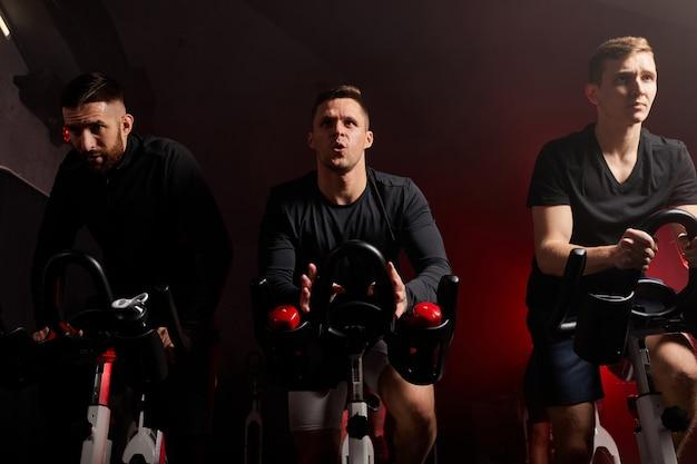 Ciclismo com concentração. jovens caucasianos com corpos perfeitos em roupas esportivas andando de bicicleta na academia